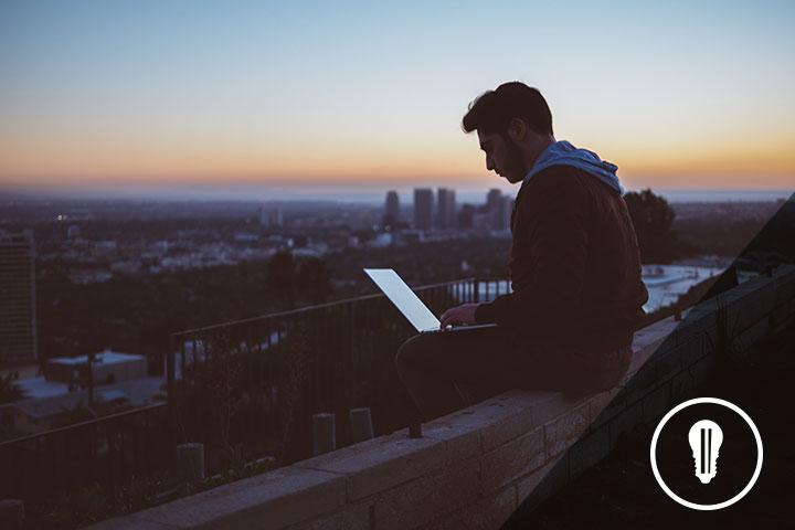 ragazzo seduto all'aria aperta mentre lavora alla propria startup innovativa
